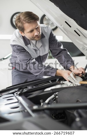 Male mechanic repairing car engine in workshop - stock photo