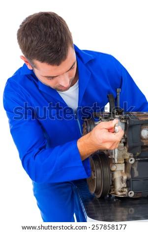 Male mechanic repairing car engine on white background - stock photo