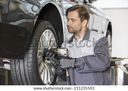 Male mechanic repairing car's wheel in workshop - stock photo