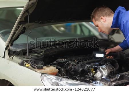 Male mechanic with flashlight examining car engine - stock photo