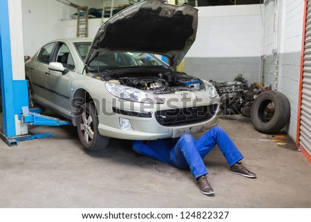 Male mechanic working under car at garage - stock photo