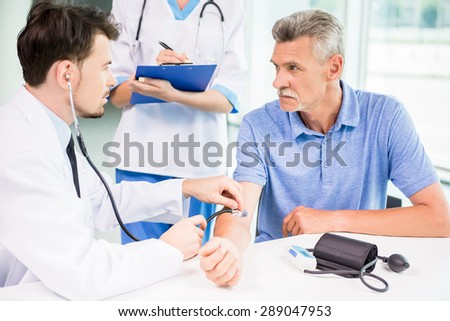 Male medical doctor examining his mature patient with stethoscope. - stock photo