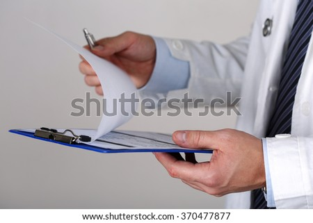 Male medicine doctor hand holding silver pen looking in clipboard closeup. Medical care, insurance, prescription, paper work or career concept. Physician ready to examine patient and help - stock photo