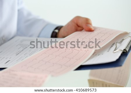 Male medicine doctor hands holding cardiogram chart on clipboard pad closeup. Cardio therapeutist assistance, physician make cardiac physical, heart rate measure document, arrhythmia concept - stock photo