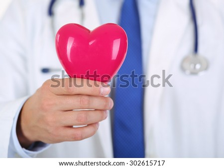 Male medicine doctor hands holding red toy heart in front of his chest closeup. Medical help, cardiology care, health, prophylaxis, prevention, insurance, surgery and resuscitation concept - stock photo