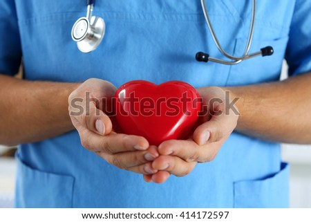 Male medicine doctor wearing blue uniform hold in hands and cover red toy heart closeup. Cardio therapeutist, physician make cardiac physical, heart rate measure, arrhythmia, old age life concept - stock photo