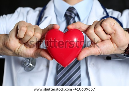 Male medicine doctor wearing hold in hands red toy heart in front of his chest closeup black background. Cardio therapeutist, physician make cardiac physical, heart rate measure, arrhythmia concept - stock photo