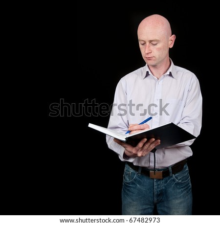 male middle age professional writting into diary - stock photo
