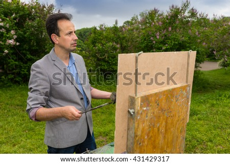 Male middle-aged creative painter looking through the park or garden standing in front of  a sketchbook during creation a sketch of his picture on a trestle and easel painting with oils and acrylics - stock photo