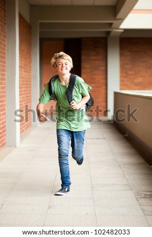 male middle school student running in school passage - stock photo
