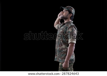Male military soldier saluting over black background - stock photo