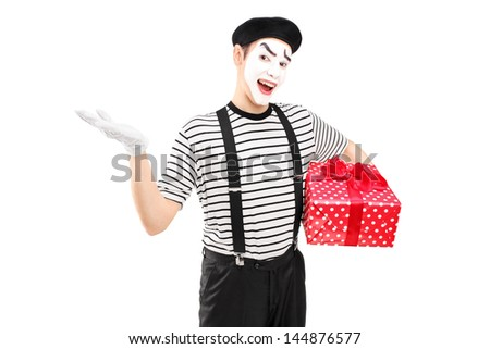 Male mime artist holding a gift box and gesturing with his hand isolated on white background - stock photo