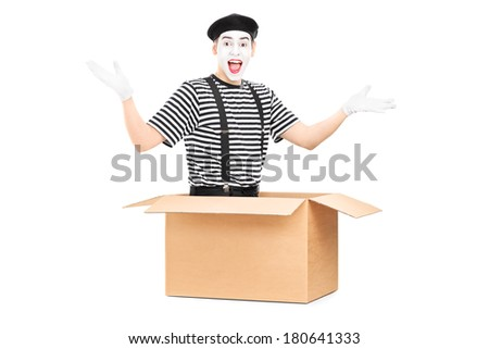 Male mime artist sitting in a carton box and gesturing with hands isolated on white background - stock photo