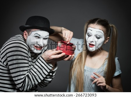 Male mime giving a gift to female mime - stock photo
