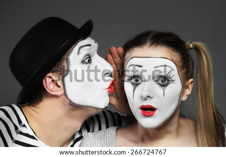 Male mime sharing secret with surprised female mime - stock photo