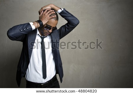 Male model poses in his sharp suit in front of grunge wall - stock photo