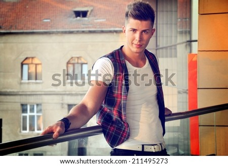 Male model posing on the terrace of a cafe - stock photo