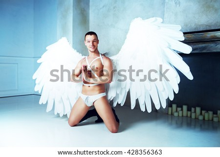 male model with big white angel wings, wearing a dance costume, studio shot - stock photo
