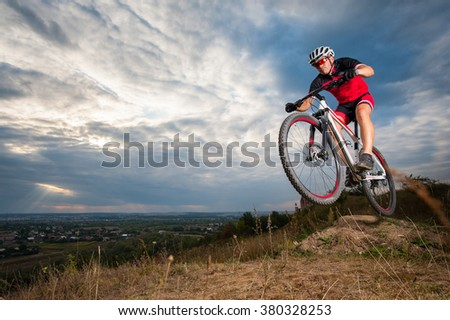 Male mountain biker jumping against blue evening sky. Low angle portrait. Extreme sport donwhill cyclist - stock photo