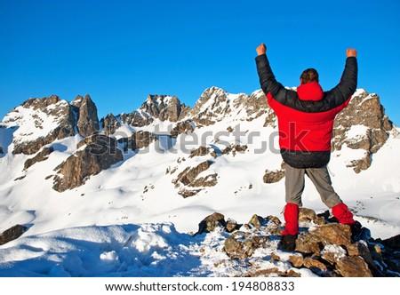 Male mountain climber raising hands on summit. - stock photo