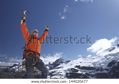 Male mountain climber raising hands with arms raised against snowy mountains - stock photo