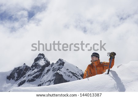 Male mountain climber reaching snowy peak against mountains and clouds - stock photo