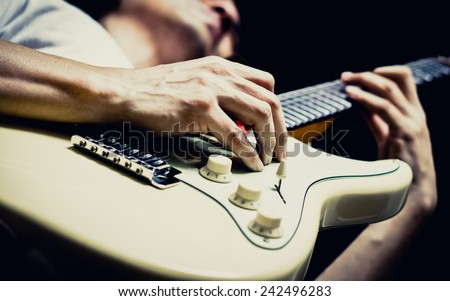 male musician playing electric guitar, isolated on black & vintage filter - stock photo