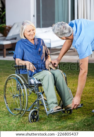 Male nurse adjusting footrest for senior woman on wheelchair in lawn at nursing home - stock photo