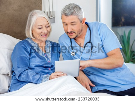 Male nurse discussing over digital tablet with senior woman in bedroom at nursing home - stock photo