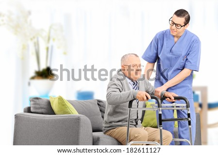 Male nurse helping an elderly gentleman to stand up in a nursing home - stock photo