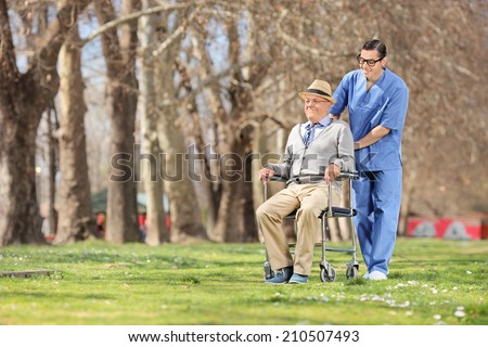 Male nurse pushing a senior in wheelchair outdoors on a sunny day - stock photo