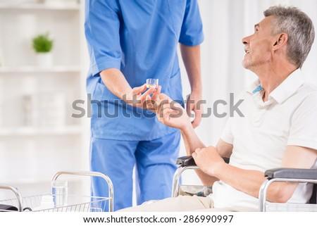 Male nurse taking pulse of senior patient at hospital. - stock photo