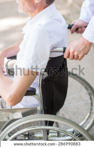 Male nurse walking with senior patient in wheelchair in garden near hospital. Close-up. - stock photo