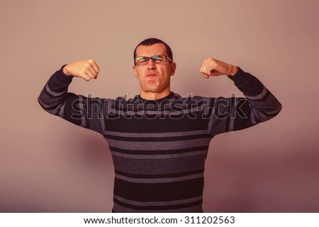 male of European appearance brunet raised his hands and shows the power of a gray background, the muscles retro - stock photo