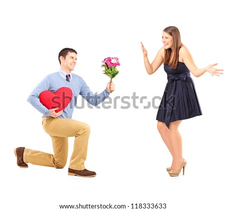 Male on knee giving a bouquet of flowers to his excited girlfriend isolated on white background - stock photo