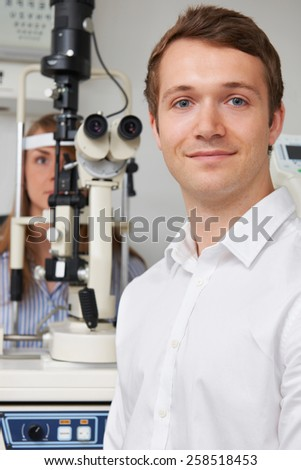 Male Optician Giving Female Patient Eye Examination - stock photo