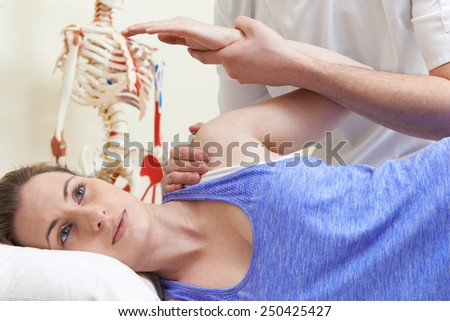 Male Osteopath Treating Female Patient With Shoulder Problem - stock photo
