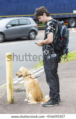 Male owner and retriever standing near crossroad, traffic in distance - stock photo
