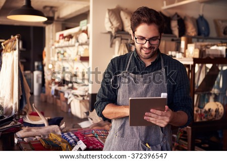 Male Owner Of Gift Store With Digital Tablet - stock photo