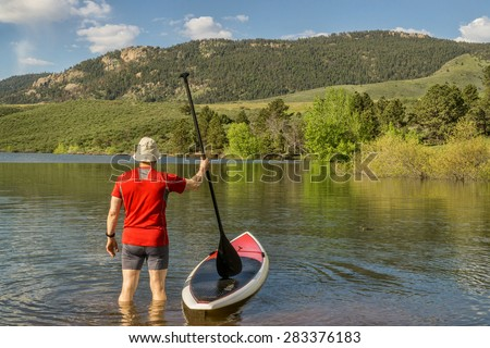 male paddler is about to step on his SUP paddleboard - a shore of Horsetooth Reservoir at foothills of Rocky Mountains, Colorado in early summer - stock photo