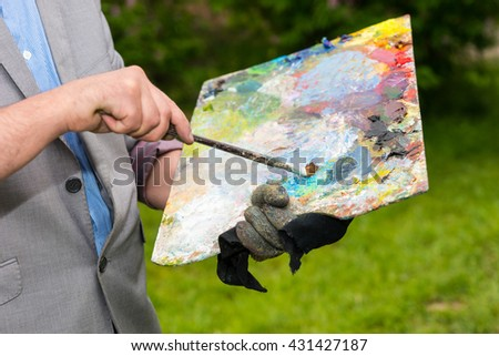 Male painter holding a colorful palette and a paintbrush mixing colors in front of a sketchbook during an art class outdoors - stock photo