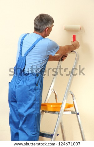 Male painter paints wall in room close-up - stock photo