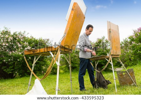 Male painter standing with two professional sketchbookes during an art class outdoors - stock photo