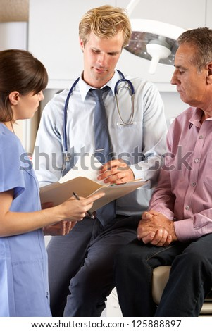 Male Patient Being Examined By Doctor And Intern - stock photo