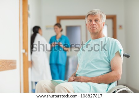 Male patient in a wheelchair looking at camera in hospital corridor - stock photo