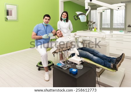 Male Patient With Dentist And Assistant In A Dental Treatment - Wearing Masks And Gloves - stock photo