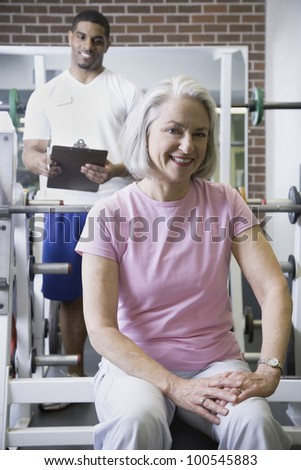 Male personal trainer with female client at gym - stock photo