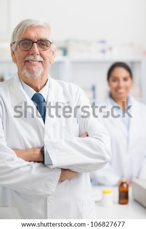 Male pharmacist looking at camera in hospital - stock photo