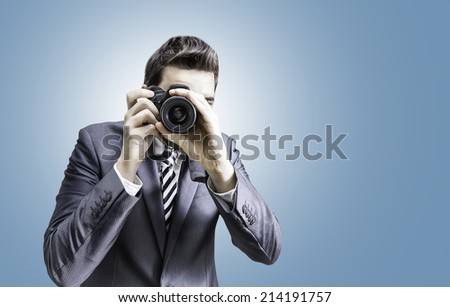 Male photographer focusing and composing an image with his professional digital SLR camera pointing the lens directly at the viewer on blue background - stock photo