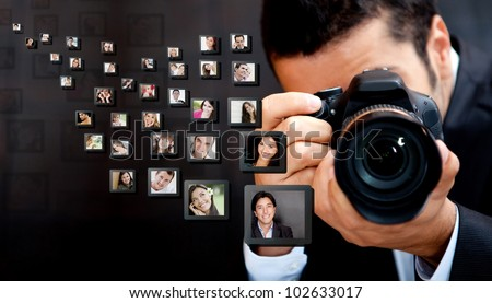 Male photographer holding the camera with pictures flying around - stock photo